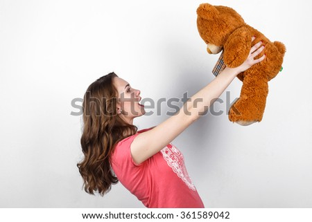 Stylish beautiful girl with long dark wavy hair in pink shirt holding in hands big brown teddy bear, gift in Valentine's Day - stock photo