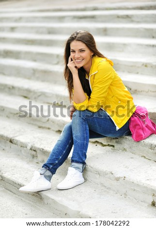 Stylish beautiful teen girl sitting on a stairs in colorful clothes  - stock photo