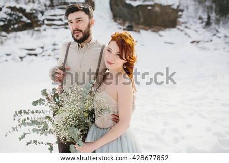 Stylish beautiful young couple bride and groom on the background of a winter landscape