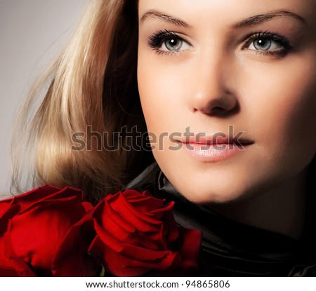 Stylish beautiful young woman holding red roses bouquet, closeup on gorgeous face, tender flowers, blond female over dark background, Caucasian model girl with fresh plant, lady in love concept - stock photo