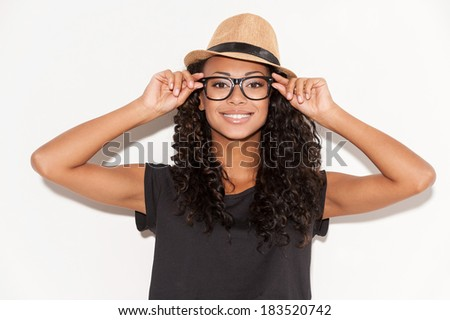 Stylish beauty. Beautiful young African woman in glasses and funky hat adjusting her glasses and smiling at camera while standing against white background - stock photo
