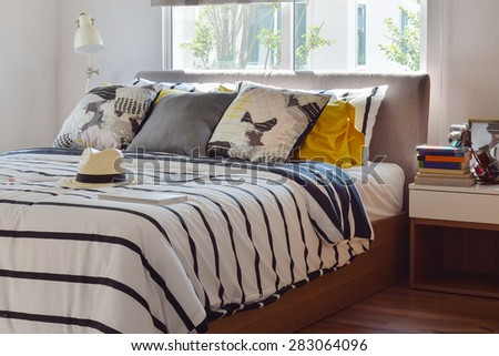 stylish bedroom interior with black and white patterned pillows on bed and decorative table lamp. - stock photo