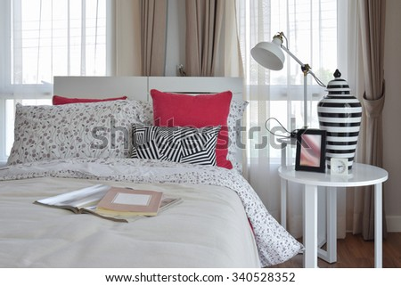 stylish bedroom interior with flower pattern pillows and decorative table lamp - stock photo