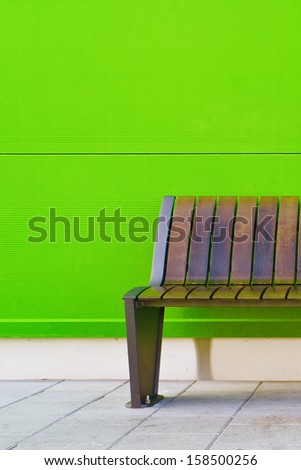 Stylish bench against green wall as background