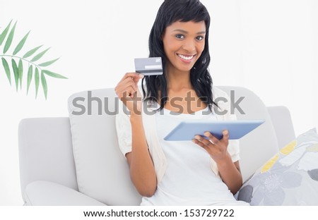Stylish black haired woman buying online with her tablet pc in a living room - stock photo