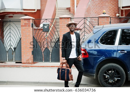 Stylish black man at glasses with hat, wear on suit with handbag against luxury car. Rich african american businessman.