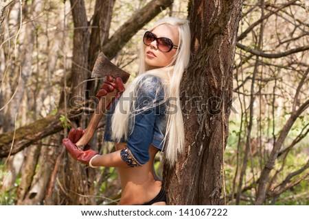 Stylish blond lady with an axe in the forest - stock photo