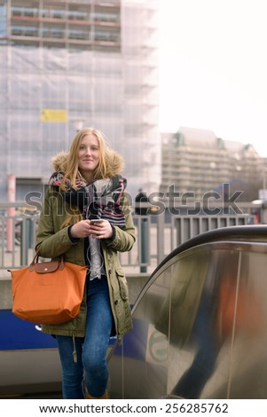 Stylish Blond Woman Walking in Winter Style Fashion While Holding his Mobile Phone with her Elegant Orange Leather Bag on her Arm. - stock photo