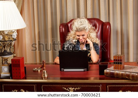 stylish blond working on a laptop at the wooden desk - stock photo