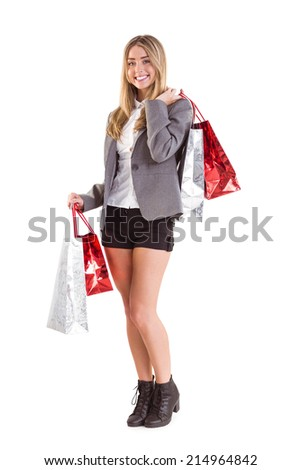 Stylish blonde holding shopping bags on white background - stock photo