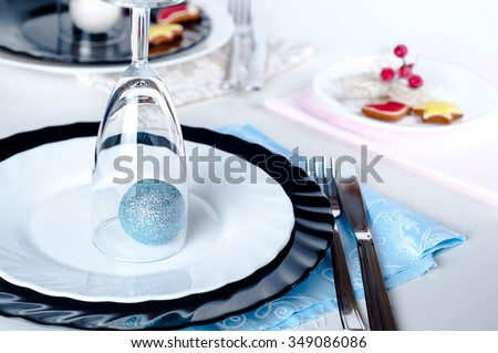 Stylish blue and silver Christmas table setting on white and black dinnerware with New Year with a blue ball under the glass - stock photo