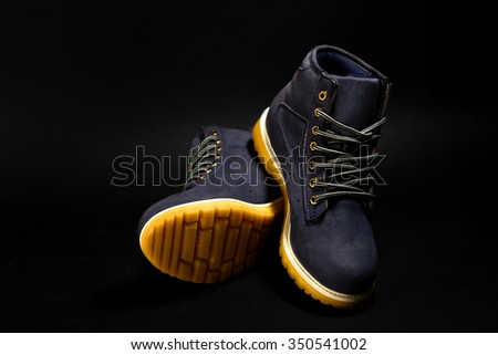stylish blue nubuck mens boots on black background, advertising concept - stock photo