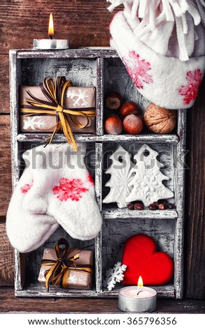 Stylish box with Christmas decorations of mittens, symbolic trees,hearts and gifts