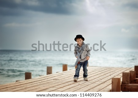Stylish boy in a hat standing on a wooden bridge on the background of the sea - stock photo