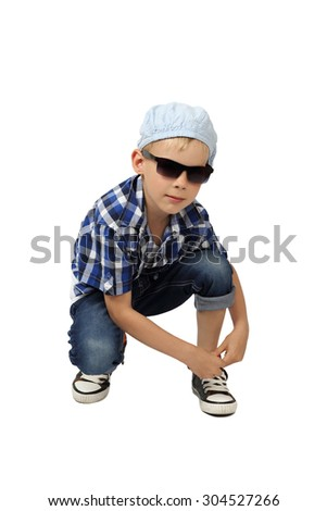 Stylish boy in plaid shirt, cap, jeans with rolled up trouser, sneakers and sunglasses sat down to tie the lace isolated on white background