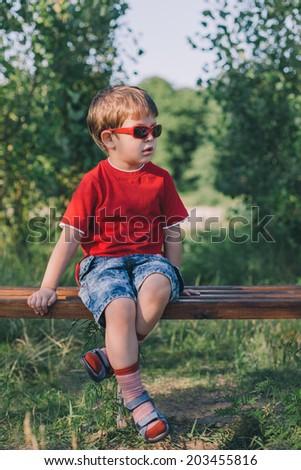 stylish boy in sunglasses sitting on bench outdoors  - stock photo