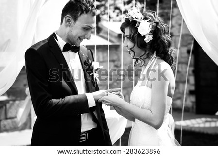 stylish bride and groom are exchange rings on the background spring garden