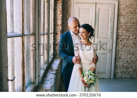 Stylish bride and groom, embrace a window in a room with white brick. Loft - stock photo