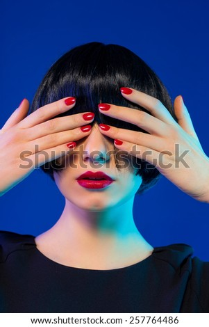 stylish brunette bob haircut closes her eyes with hands. red manicure. red lips - stock photo