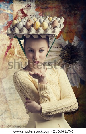 stylish brunette girl with yellow dress posing in Easter portrait with funny eggs box on the head, send a kiss and looking in camera  - stock photo