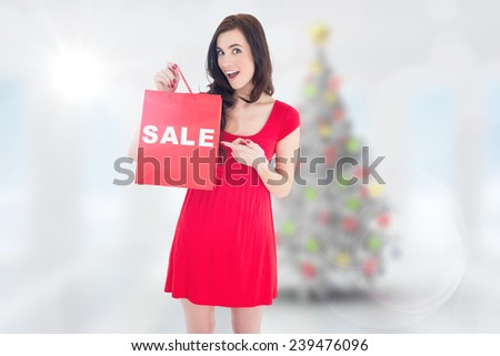 Stylish brunette in red dress showing sale bag against blurry christmas tree in room - stock photo