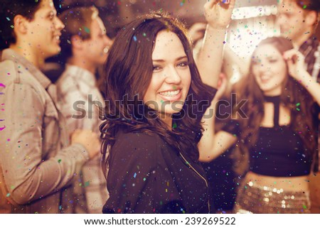 Stylish brunette smiling at camera against flying colours - stock photo