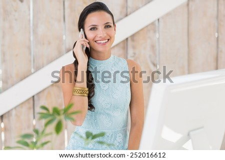 Stylish brunette smiling at camera in her home office