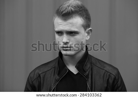 Stylish bully concept. Portrait of brutal young man with short wet hair wearing black jacket and posing over urban background. Hipster style. Close up. Black and white outdoor shot