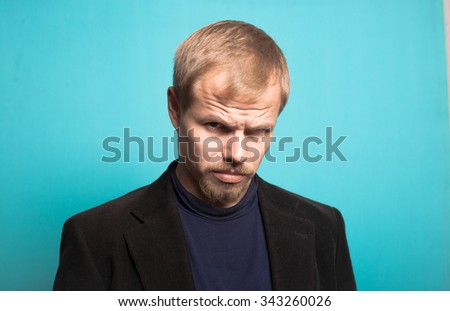 stylish business man angry with a beard and mustache, office style studio shot on isolated blue background - stock photo