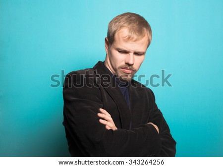 stylish business man folded his arms crosswise, with a beard and mustache, office style studio shot on isolated blue background - stock photo
