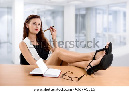 stylish business woman thinking about something at her office desk. - stock photo