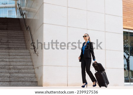Stylish business woman with luggage walking along the street - stock photo