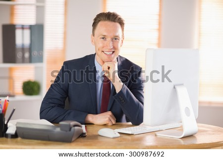 Stylish businessman smiling at camera in his office