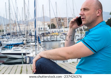 """Stylish businessman using his """"smart phone"""" while sitting near a marine with luxury yachts against a deep blue sky and sea. - stock photo"""