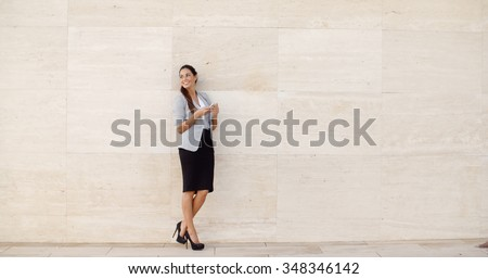 Stylish businesswoman standing against a neutral cream colored wall holding her mobile phone and looking back over her shoulder  full length with bilateral copyspace - stock photo