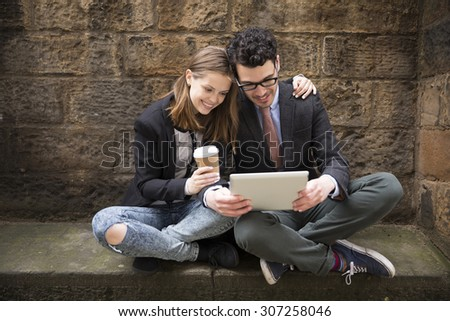 Stylish Caucasian couple using a digital tablet outdoors in the city. - stock photo