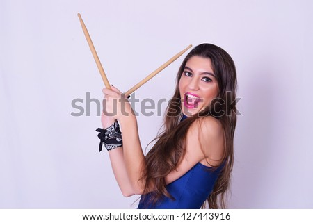 Stylish caucasian young woman holding drum sticks, isolated over grey background. Urban and rock concept. Girl power. - stock photo