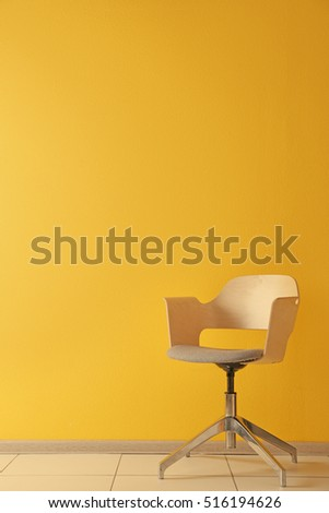 Stylish chair on yellow wall background