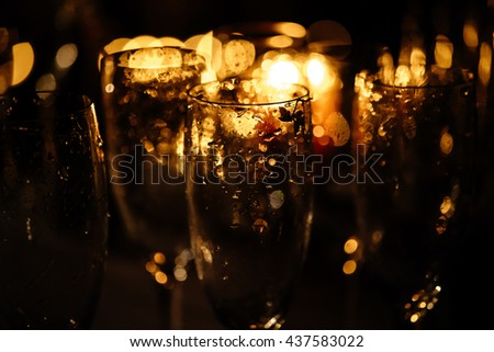 stylish champagne glasses empty on background of warm romantic candle light at evening wedding ceremony - stock photo
