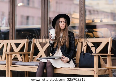 Stylish charming hipster girl thoughtfully looks aside while resting after work on laptop computer, young female student holding closed net-book on knee while sitting with cup on coffee on the street - stock photo