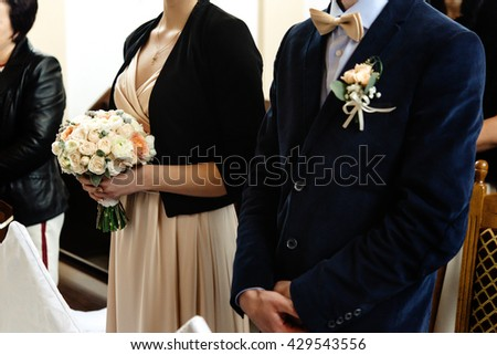 stylish chauffeur and bridesmaid holding bouquet at wedding ceremony at church - stock photo
