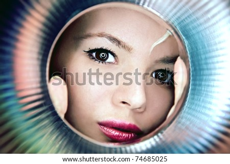 Stylish close-up portrait of young girl observing through metal object. - stock photo
