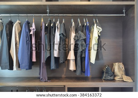 Stylish cloths in dark shade hanging in open wooden wardrobe  - stock photo