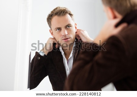 Stylish confident young man looking at himself in mirror