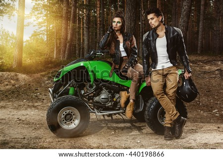Stylish couple and ATV in the forest