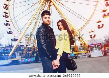 Stylish couple in love holds hands and enjoying together being in an amusement park . Trendy hipster outfit .bright colors. Odessa. - stock photo