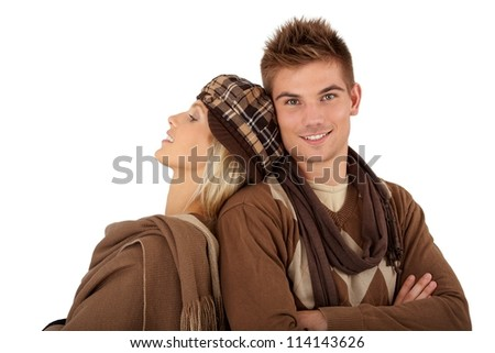 Stylish couple in winter clothes, girlfriend leaning on boyfriend smiling at camera. - stock photo