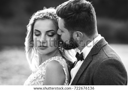 Stylish couple of happy newlyweds posing in the park on their wedding day. Perfect couple bride, groom posing and kissing. Sexy kissing stylish couple of lovers close up portrait . black and white