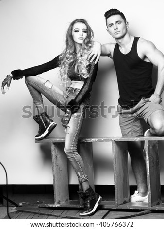 Stylish couple. Shot of a fashionable couple posing at studio, black and white