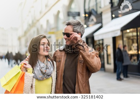 Stylish couple walking in a cobbled car-free street. The grey hair man with beard is wearing sunglasses and a brown leather coat and the woman a yellow top and two shopping bags, they also have scarfs